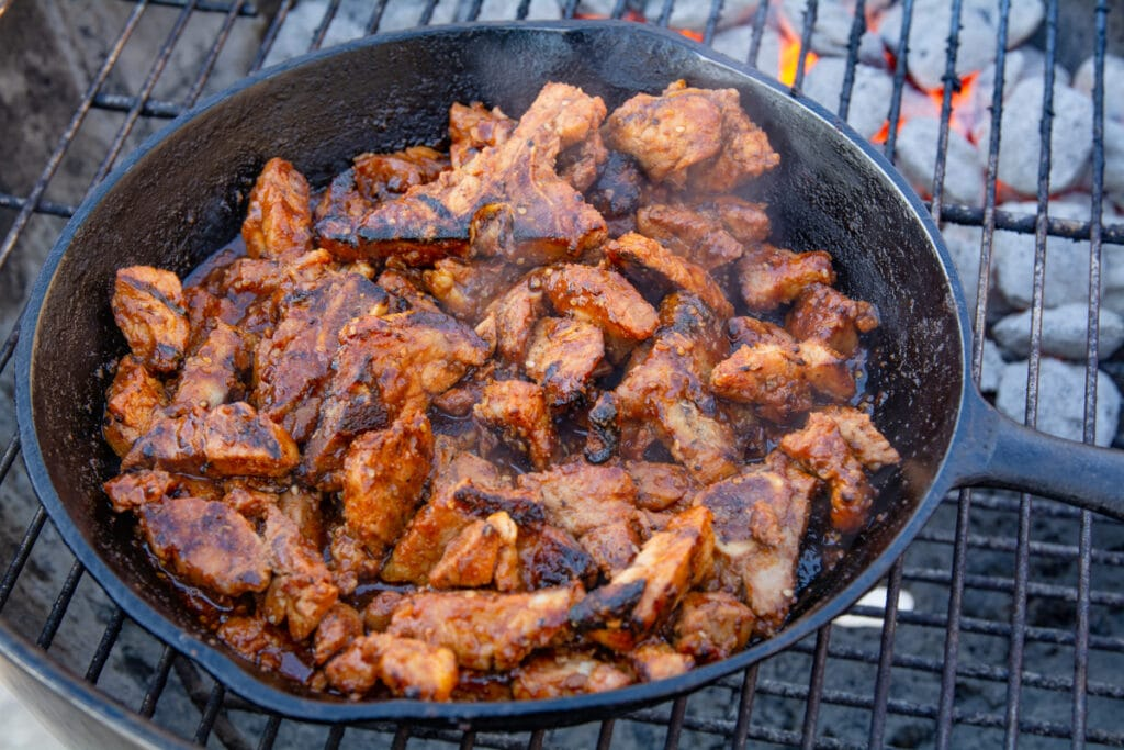 Spicy pork in a cast iron pan cooking on a grill.