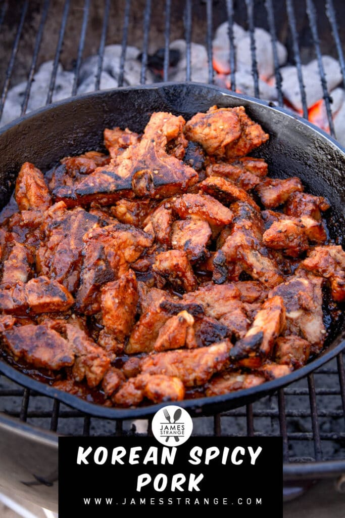 Spicy pork in a cast iron pan cooking on a grill. This is a pin for pinterest