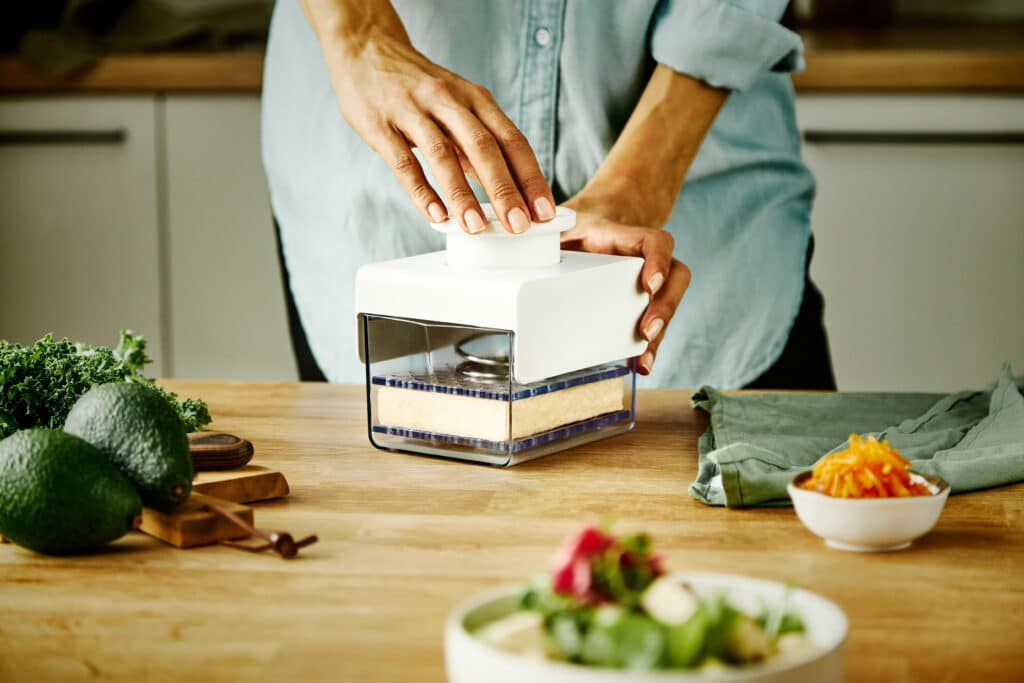 Someone using a tofu press to press tofu