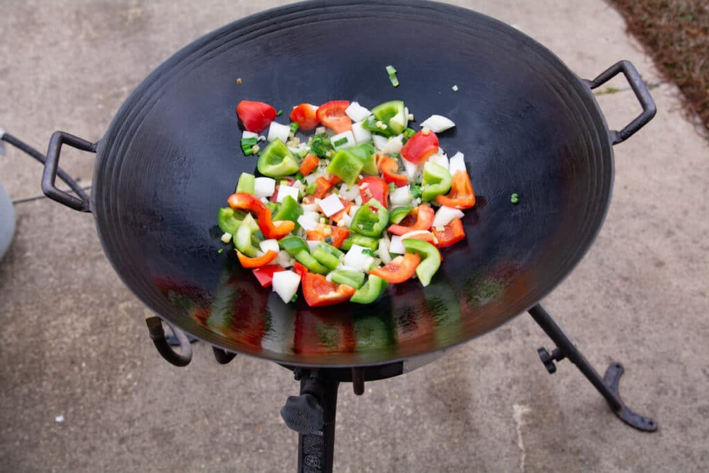 Bell peppers, green onion, garlic and ginger in a wok.