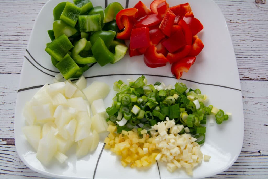 Ginger, garlic, onions, and bell peppers cut up and on a plate