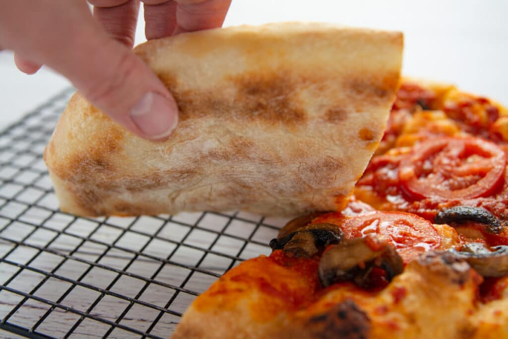 A hand lifting a slice of pizza showing the bottom of the regular crust.
