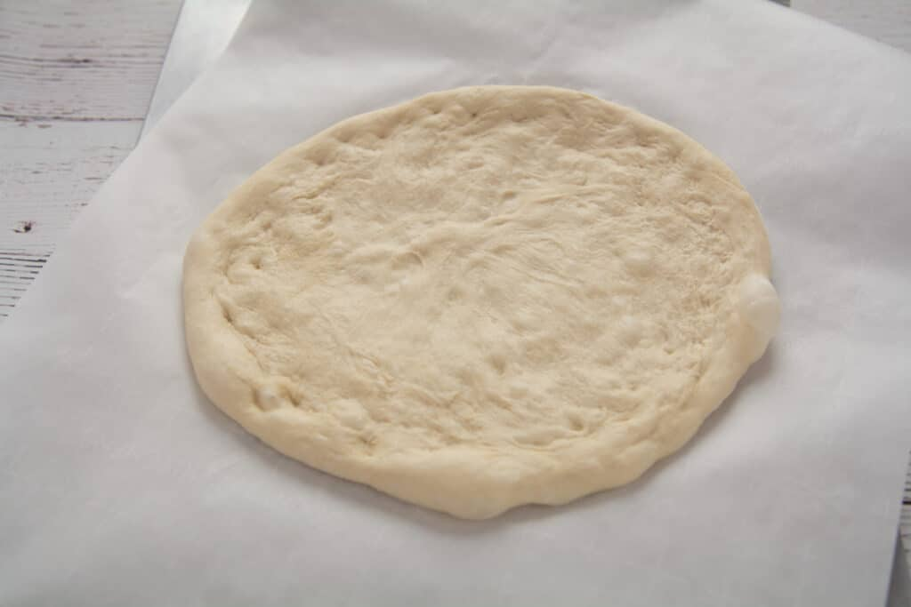 Pizza dough stretched out and formed into a pizza on parchment paper.