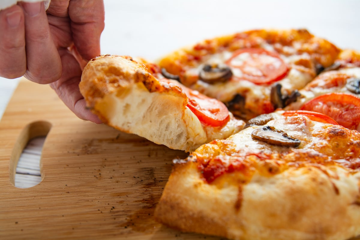 A hand lifting a slice of pizza showing the air pockets in the regular crust.