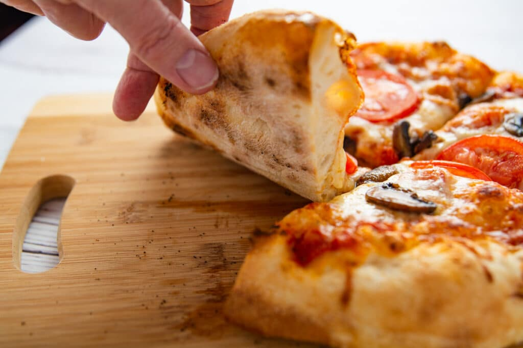 A hand lifting a slice of pizza showing the bottom with black spots of the regular crust.