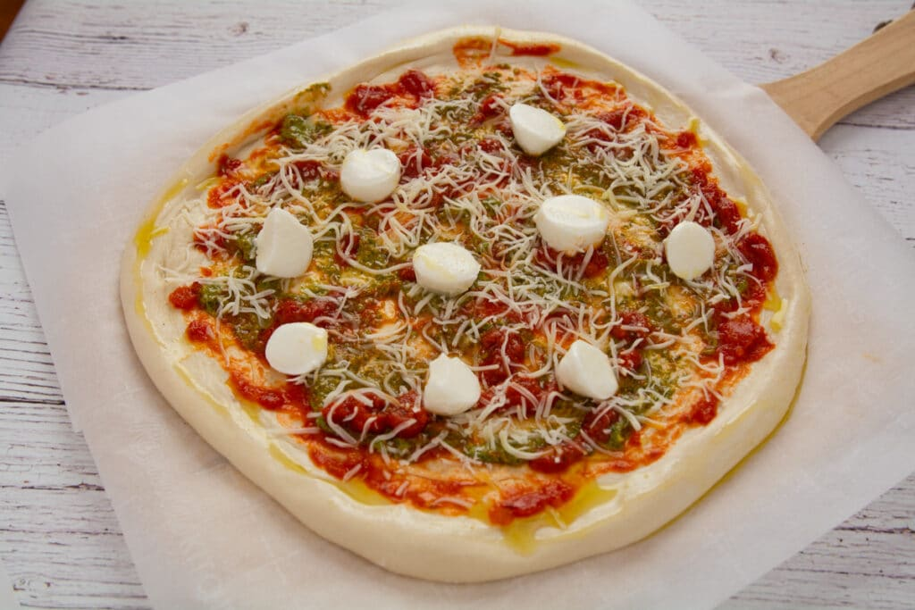Pizza ready for the oven on parchment paper