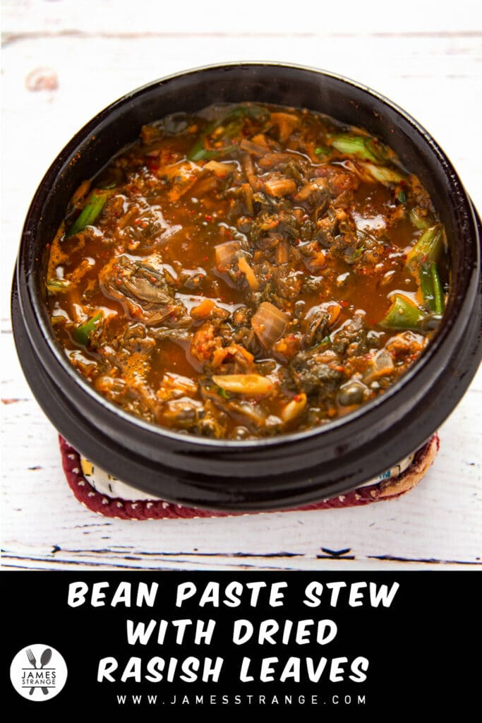 Ceramic bowl of Korean stew on a table. This is a pin for Pinterest